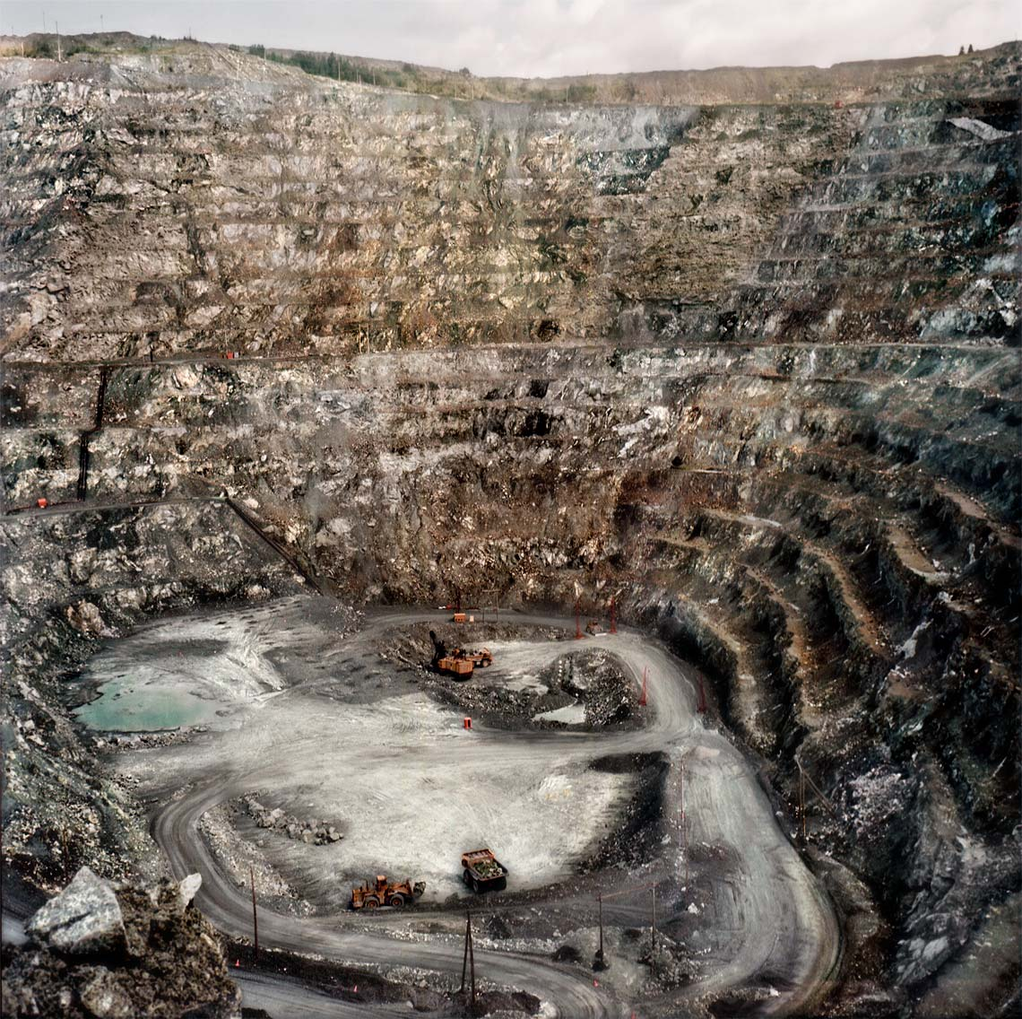 Looking downward into mine pit with high grey sides of scraped rock