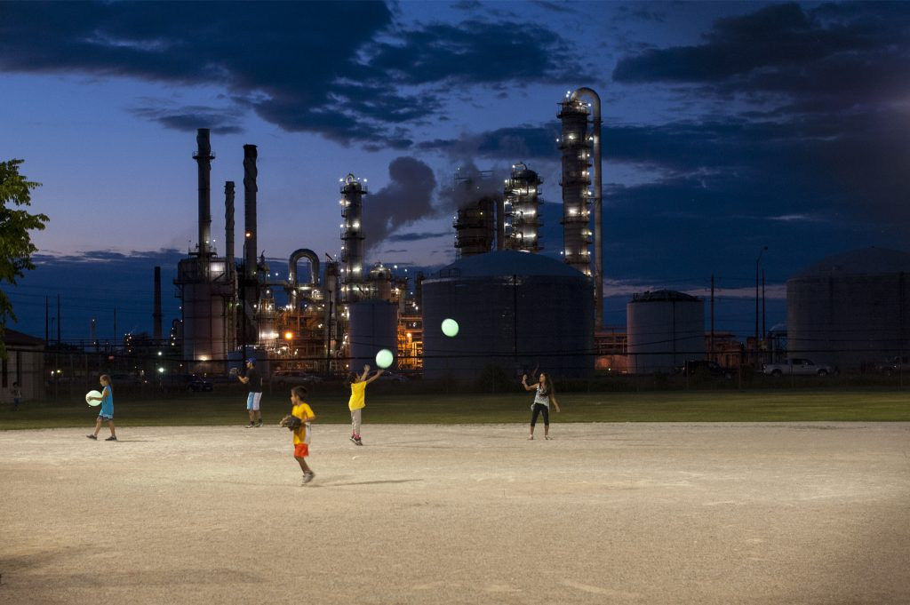 Three children playing on illuminated field, industrial buildings and twilight sky in background