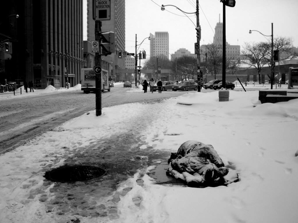 A figure lies down on the bare floor of a local street in black covering on a black mat. The figure is covered with a light settlement of snow. The floor around him is completely covered in snow and the sidewalk beside him has many footprints. Behind the figure is a busy intersection where 3 figures are crossing the road as 4 cars wait for them. One can see some buildings off into the distance and a Coke truck drives down the road parallel to the sleeping figure.