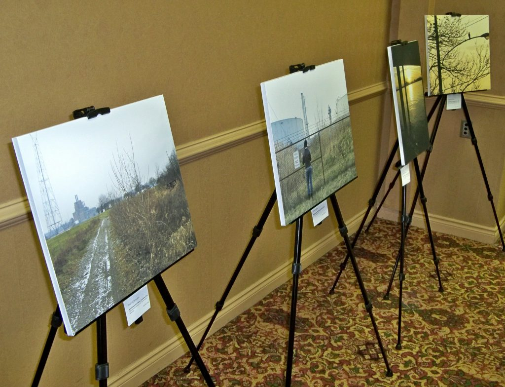 In the corner of a conference room, four prints of photographs are being displayed on metal stands that are lined up next to each other. From left to right, the prints respectively depict a trail surrounded by greenery, a person standing in front of a fence enclosing a refinery tower, light on water, and a streetlight against a background of trees and a yellow sky.