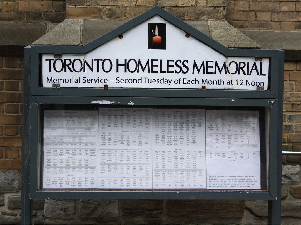 "A signboard shaped like a house divided into two parts that sits in front of a building made from brick. The signboard is large on the image and it reads ""TORONTO HOMELESS MEMORIAL"" in big bold letters and ""Memorial Service – Second Tuesday of Each Month at 12 Noon"" is smaller lettering below the big letters. The sign seems weathered as the black paint on the borders of the sign are fading and chipped. The lower half of the sign states individual names that are illegible because of the camera angle and the glaring light bouncing off the glass covering on the sign."
